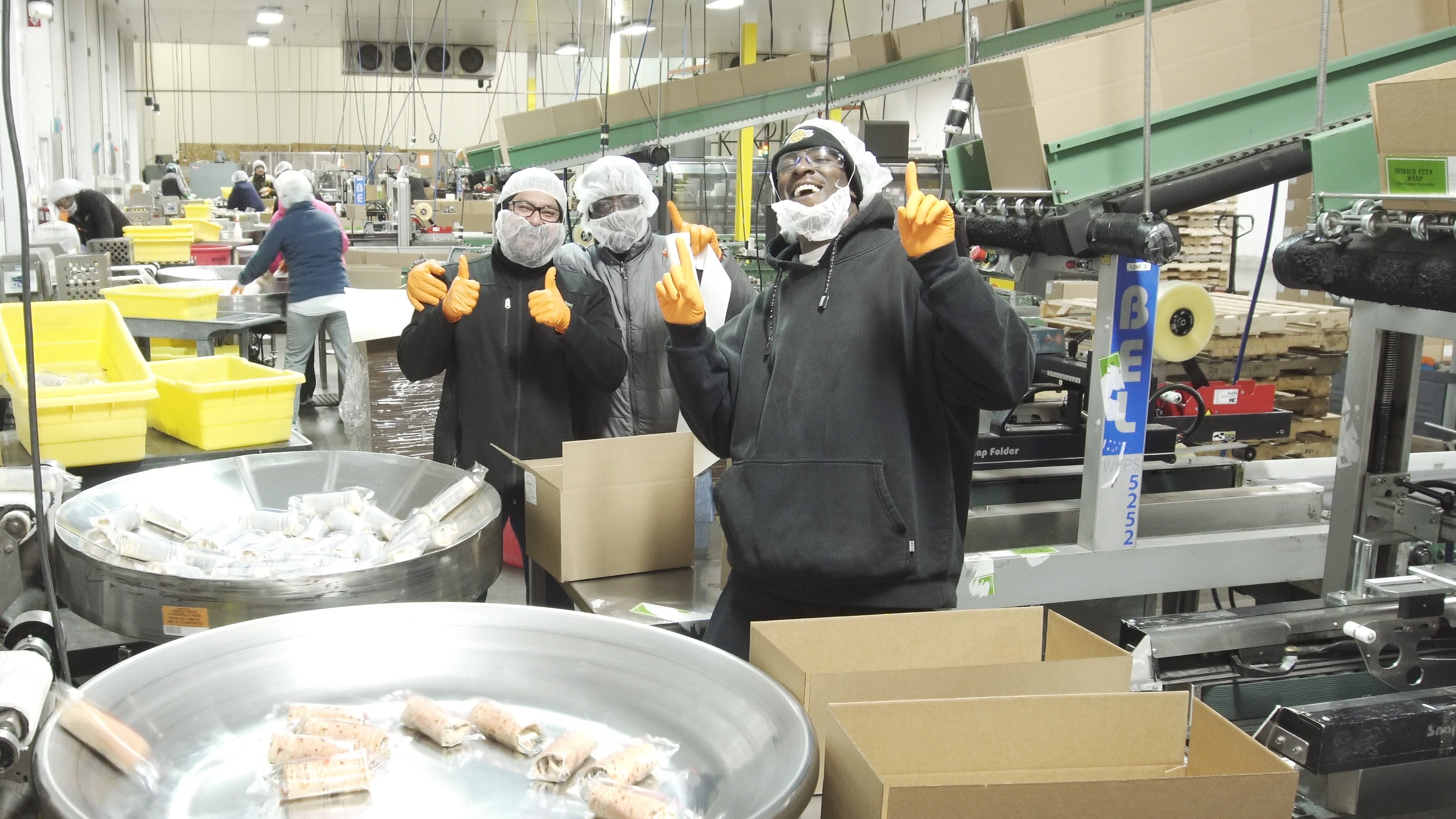 Contract manufacturing workers give the thumbs up while packing goods